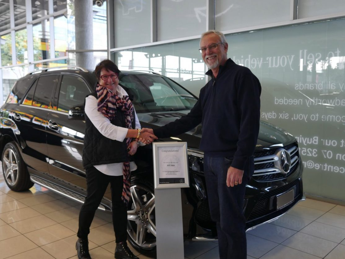 Winner Kylie with CEO collecting her new car