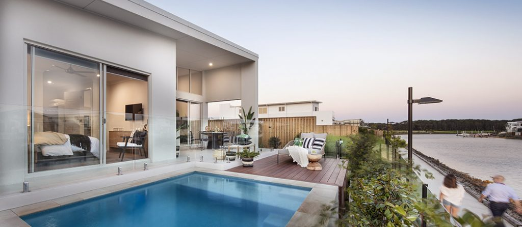 Waterfront outdoor setting with al fresco area and pool.